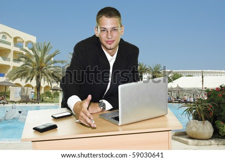 Young businessman holding hand over his desk with laptop, mouse and mobile, touristic resort with pool and hotels in the background - stock photo