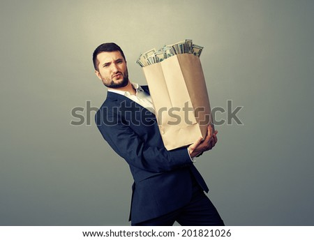 young businessman holding heavy paper bag with money over dark background - stock photo