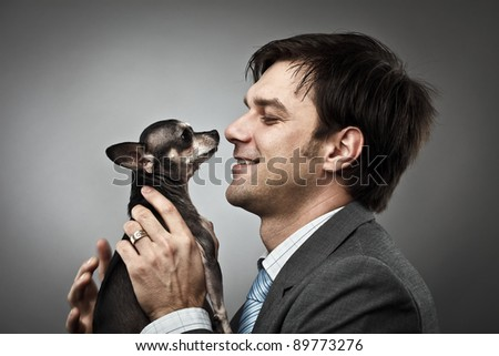 Young businessman holding his chihuahua dog pet - stock photo