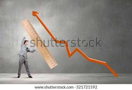 Young businessman holding in hands huge ruler
