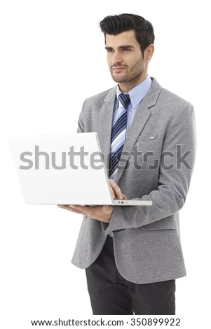 Young businessman holding laptop computer in hand, working on it. - stock photo