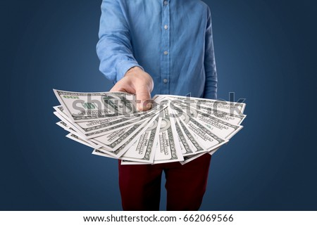 Young businessman holding large amount of bills