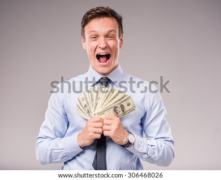 Young businessman holding more money on a gray background - stock photo