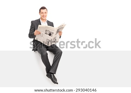 Young businessman holding newspaper seated on signboard. The newspaper is custom made, the text is Latin and the pictures are my copyright.  - stock photo