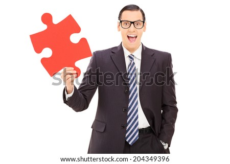 Young businessman holding red piece of a puzzle isolated on white background