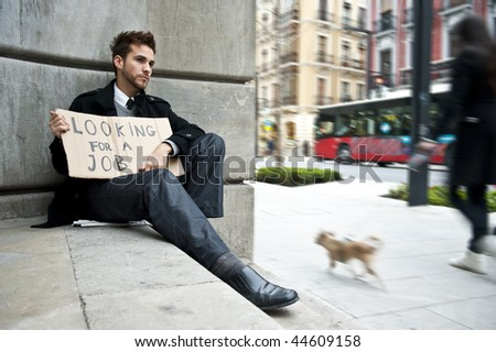 Young businessman holding sign Looking for a job - stock photo