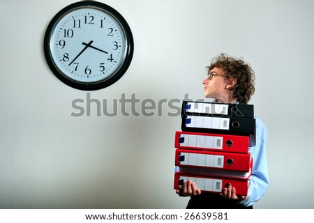 Young businessman holding stack of folders and looking at clock - stock photo