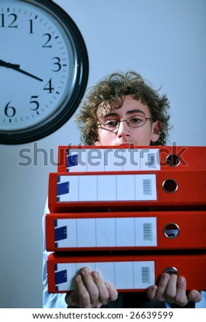 Young businessman holding stack of folders, deadline concept - stock photo