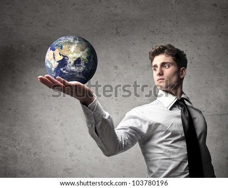 Young businessman holding the Earth in his hand [Elements of this image furnished by NASA] - stock photo