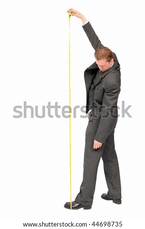 Young businessman holding yellow measuring tape and looking at the floor. - stock photo
