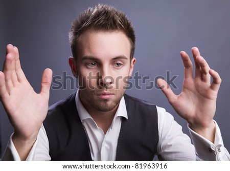 Young businessman holds on his hands empty space.