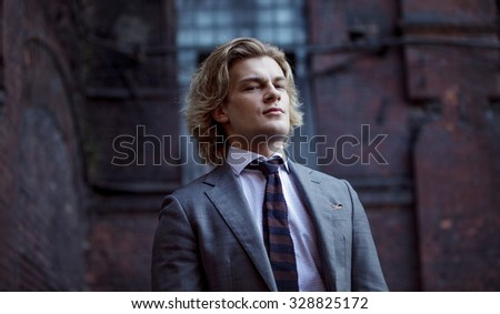 young businessman in a gray suit, business style,  portrait on the wall background