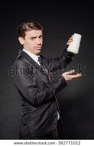young businessman in black suit holding a white blank paper cup of coffee with a white plastic cap . emotions, facial expressions, feelings, body language, signs. image on a black studio background.