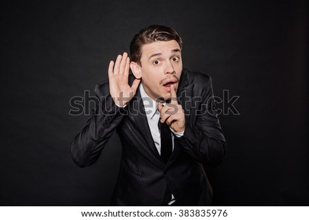 young businessman in black suit holds his hand near his ear and listening something. emotions, facial expressions, feelings, body language, signs. image on a black studio background. - stock photo
