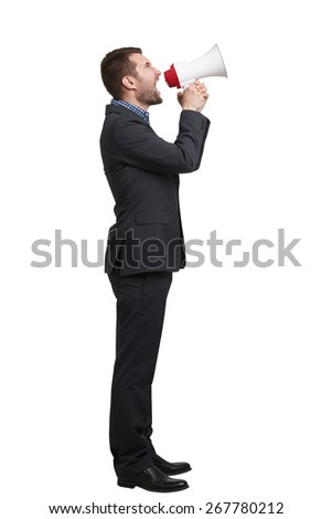 young businessman in black suit looking up and screaming at megaphone. isolated on white background