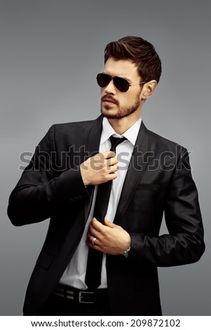 Young businessman in black suit on gray background