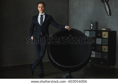 young businessman in black suit posing near the chair on gray background
