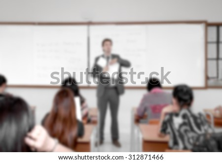 Young businessman in business classroom lecture with documents in hands with young female students - stock photo