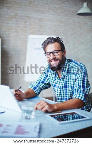 Young businessman in casualwear and eyeglasses working in office - stock photo