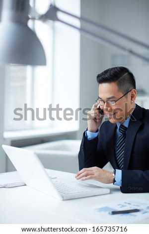 Young businessman in formalwear using laptop and calling in office - stock photo