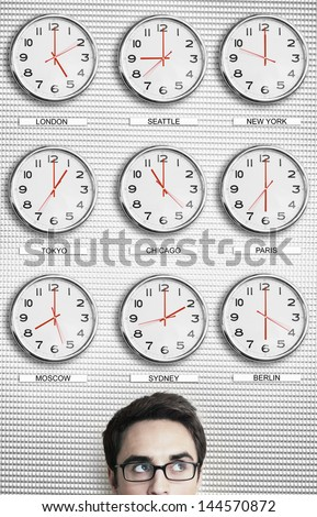 Young businessman in front of clocks showing time across the world - stock photo