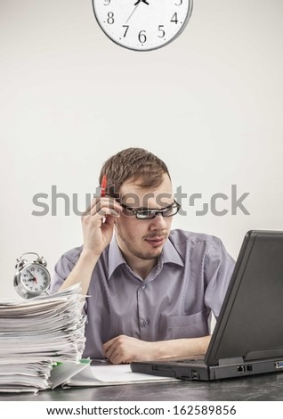 Young businessman in glasses hardworking and  looking at screen black laptop at desk in his office on background gray wall with clock Vertical - stock photo