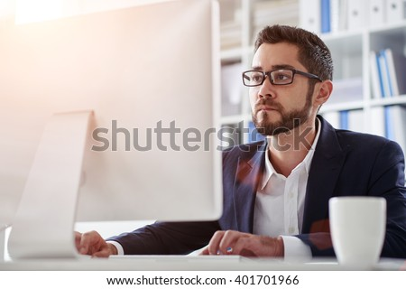 Young businessman in glasses working on computer in office