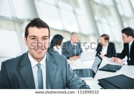Young businessman in modern office with colleagues in background - stock photo
