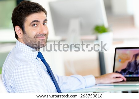 Young businessman in office thinking about something