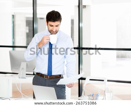 Young businessman in office with a mug and papers