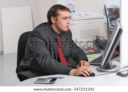 Young businessman in office works with computer - stock photo