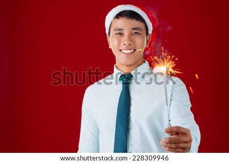 Young businessman in Santa hat holding a Bengal light - stock photo