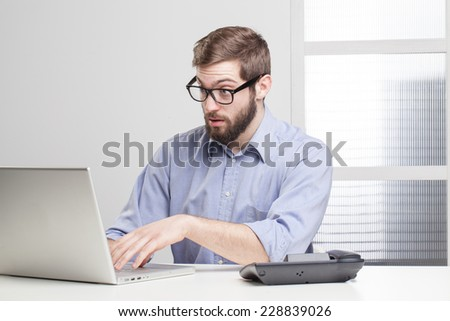 Young businessman in shock looking at his laptop  - stock photo
