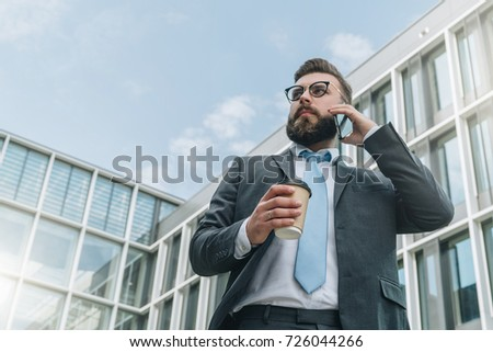 Young businessman in suit and tie is standing outdoor, drinking coffee and talking on his cell phone. In background is modern glass building. Man is working. Negotiations by phone. Business planning.