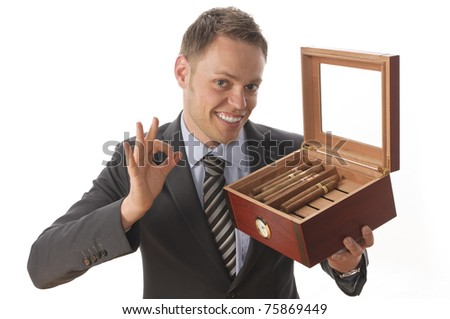 Young businessman in suit and tie, sitting at a desk and enjoy a good cigar from his humidor. Isolated against a white background