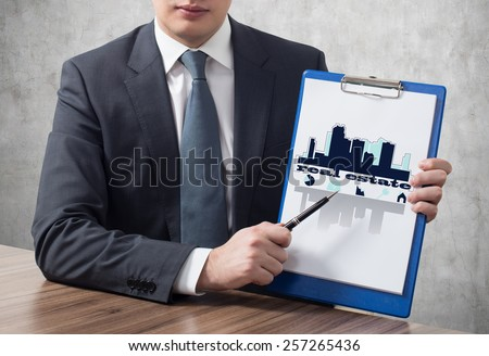 young businessman in suit holding clipboard with real estate concept - stock photo