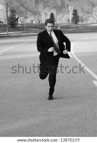 young businessman in suit running down the middle of an empty road - stock photo