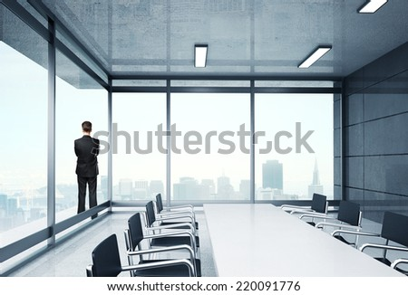 young businessman in suit standing in big office