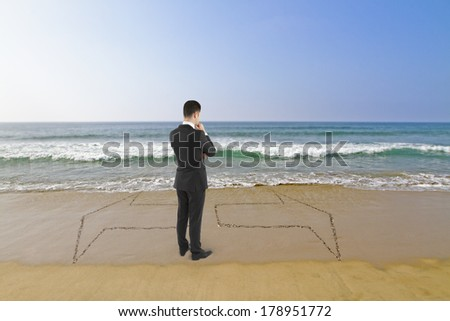 young businessman in suit standing on beach