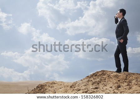 Young businessman in sunglasses standing in the desert and talking on phone - stock photo