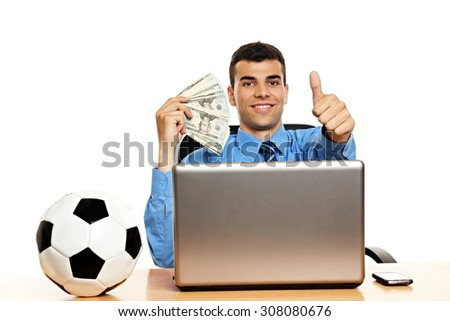 Young businessman in the office shows you money and thumb up - stock photo