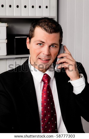 Young businessman in the office with phone - stock photo