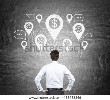 Young businessman in white shirt and black pants thinking about future prospects in front of blackboard wall. Concept of decision making. - stock photo