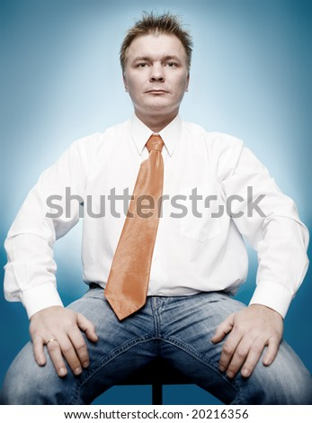 young businessman in white shirt and orange tie on blue background - stock photo