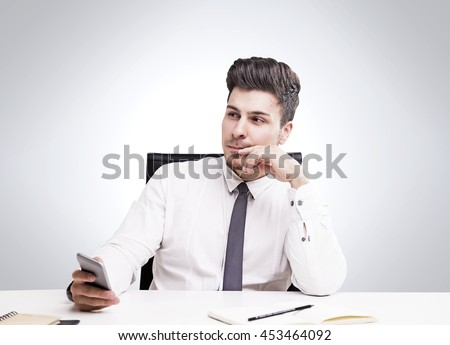 Young businessman in white shirt and tie thinking about future sitting in armchair. Concept of decision making. Mock up - stock photo