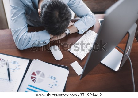 Young businessman in white shirt sleeping on the desk in the office among the documents - stock photo