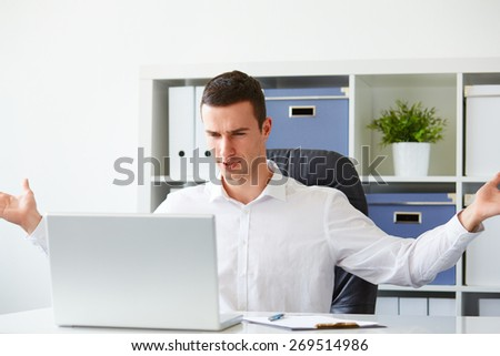 Young businessman is angry while working on laptop - stock photo