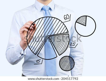 Young businessman is drawing pie charts as a metaphor of business development activity and implementation of new ideas. - stock photo