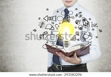 Young businessman is holding a book with flying around business icons and a light bulb as a concept of the new business ideas. - stock photo