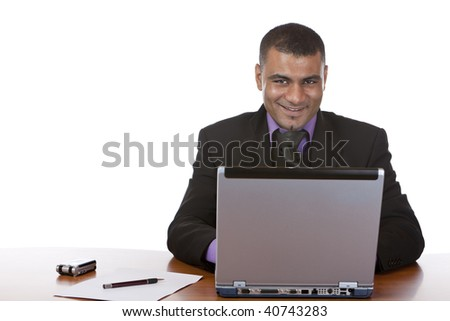 Young businessman is sitting in his office, works on laptop and smiles into camera. Isolated on white. - stock photo